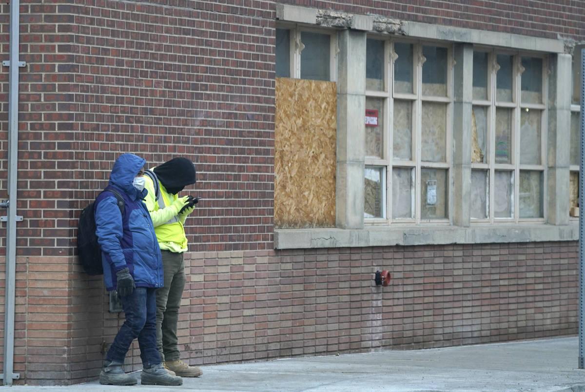 Un par de trabajadores usan cubrebocas mientras esperan un paseo fuera de una obra a finales de ...