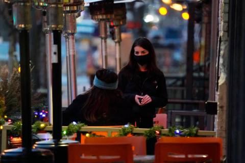 Un camarero lleva un cubrebocas mientras atiende a un cliente sentado en el patio exterior de u ...