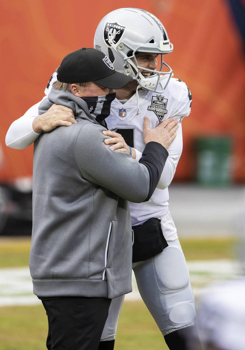 El entrenador Jon Gruden, izquierda, abraza al mariscal de campo de los Raiders, Derek Carr (4) ...