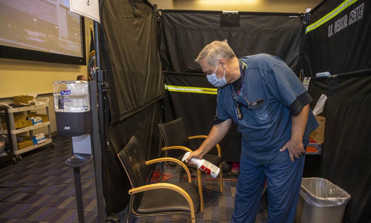 El enfermero Darrel Cowlishaw desinfecta su vaina mientras algunos de los primeros veteranos de ...