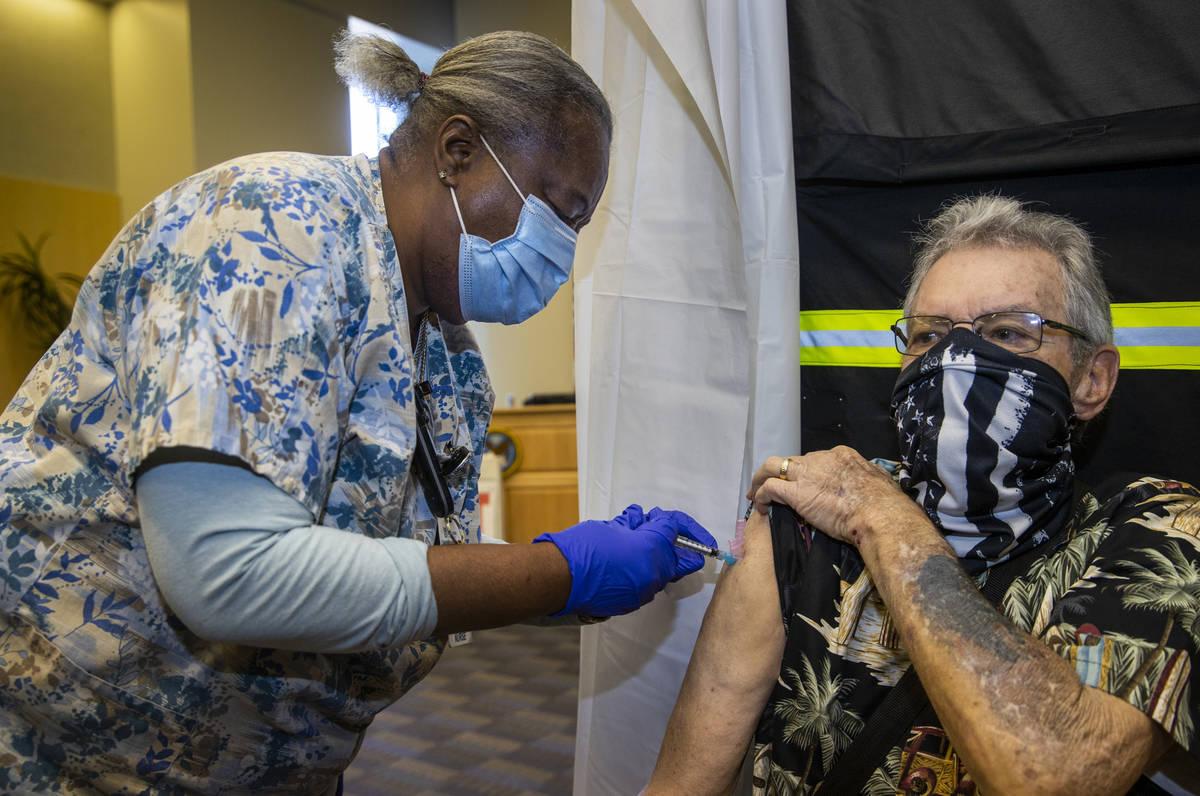 La enfermera Francine Jones-Toliver, a la izquierda, inyecta al veterano George Davis mientras ...