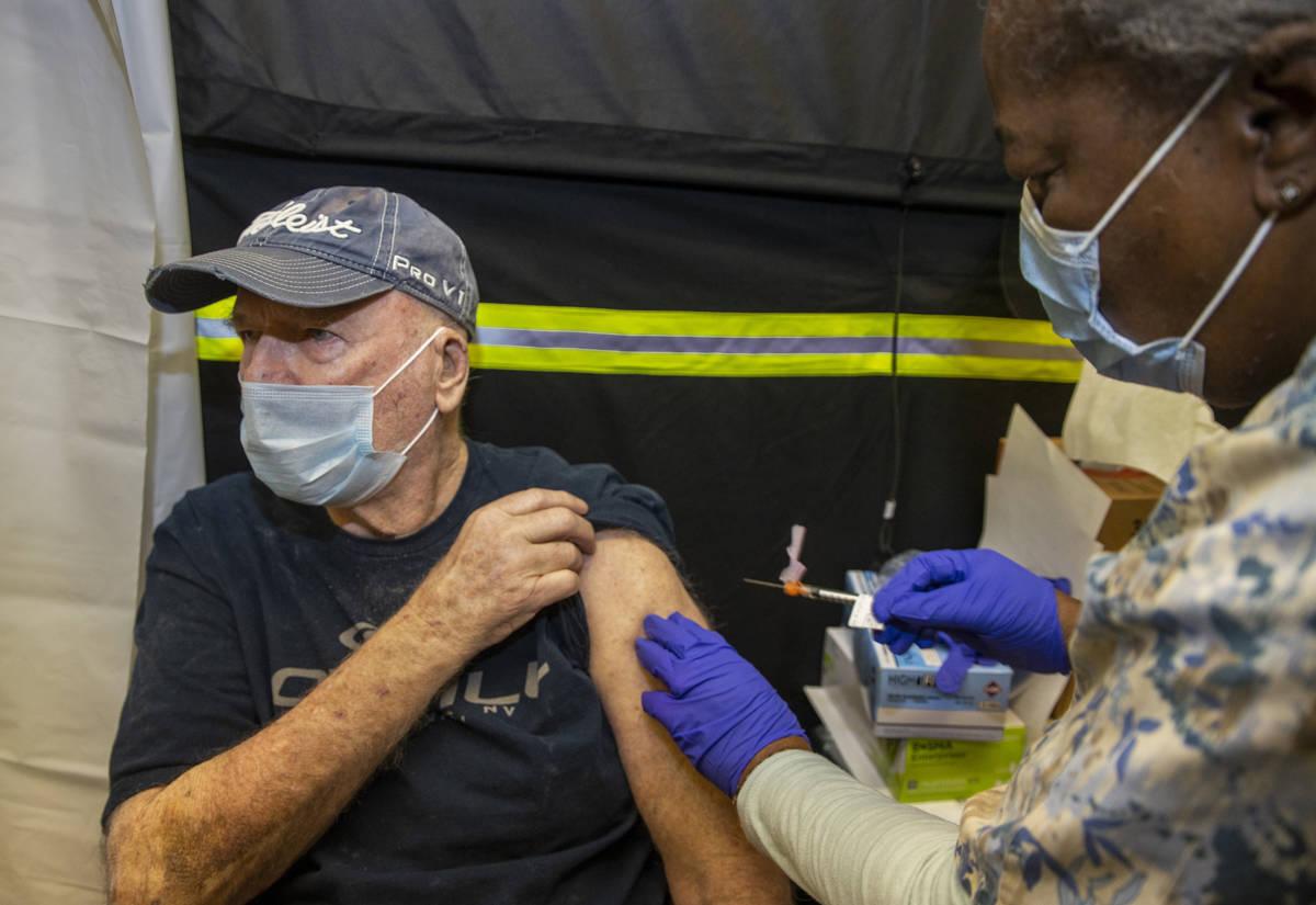 El veterano Jack Daughtrey, izquierda, recibe una inyección de la enfermera Francine Jones-Tol ...