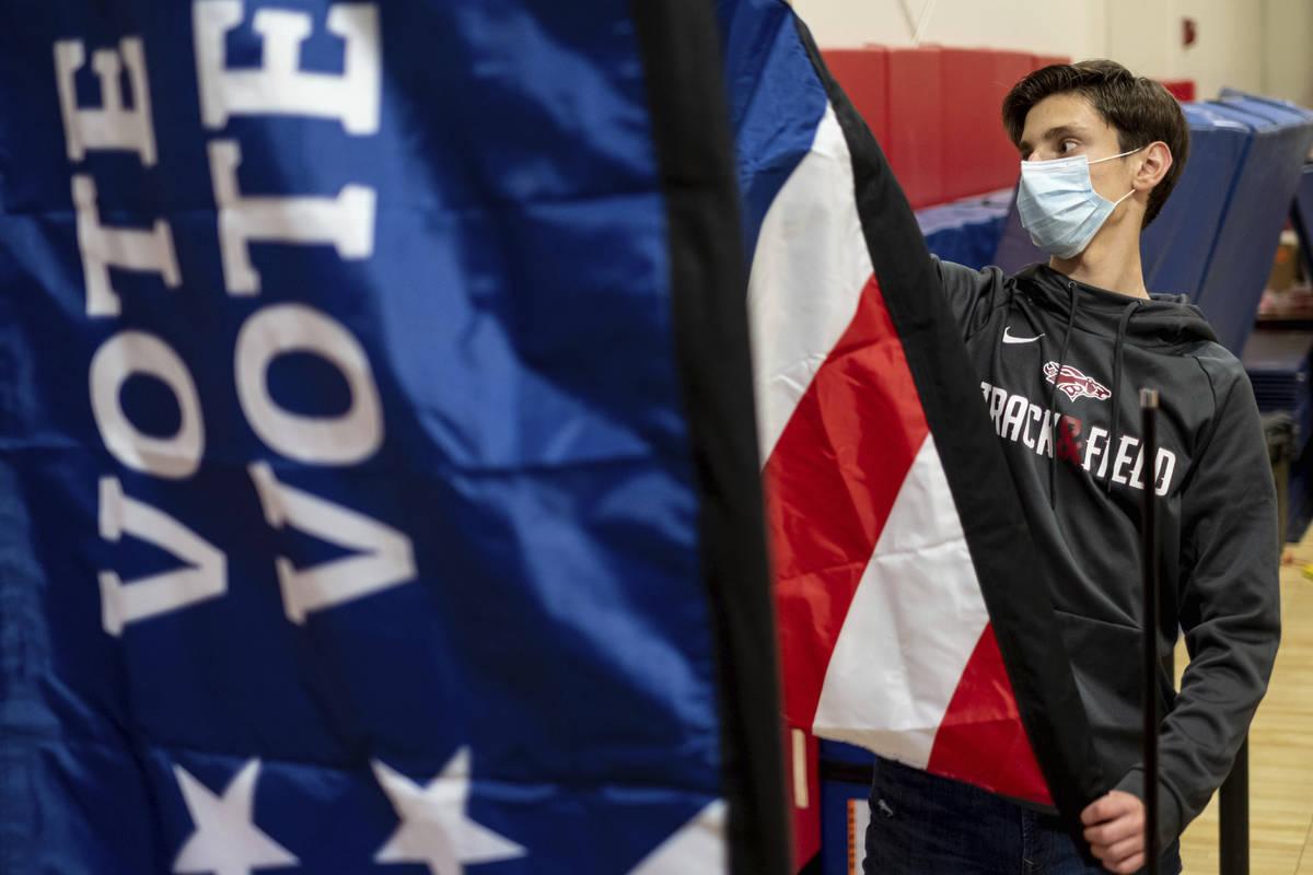 Thomas Hedrich coloca banderas de votación en un centro de votación en el condado de Gwinnett ...