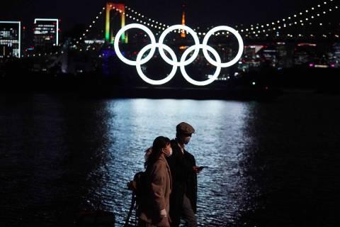 En esta foto de archivo del 1 de diciembre de 2020, un hombre y una mujer pasan cerca de los an ...