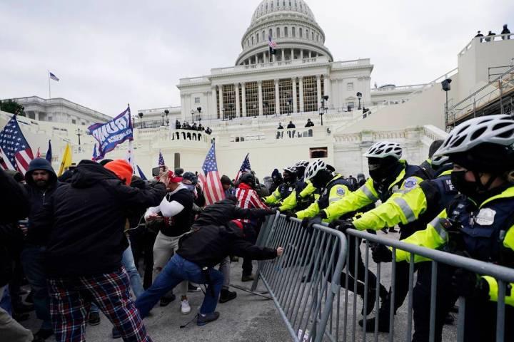 En esta foto de archivo del 6 de enero de 2021, los partidarios de Trump intentan atravesar una ...
