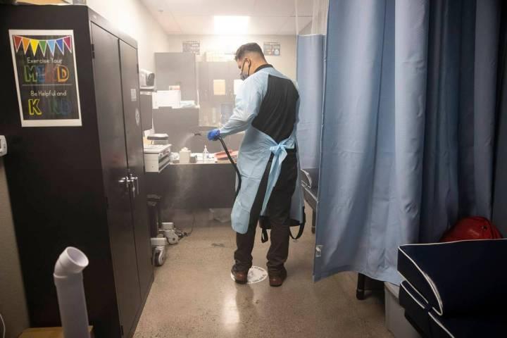 El conserje escolar Gabriel González rocía la enfermería con un desinfectante en Mater Acade ...