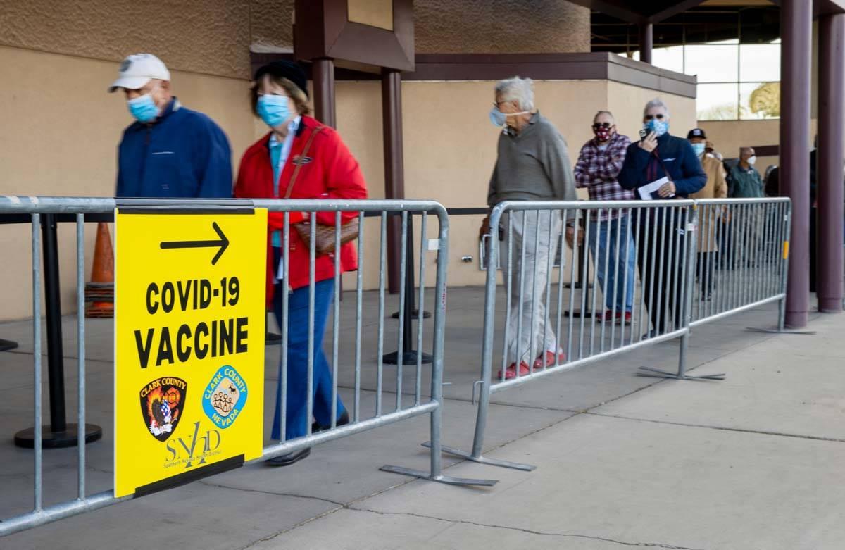 La gente se mueve a lo largo de la fila para entrar en Cashman Center para las vacunas contra C ...
