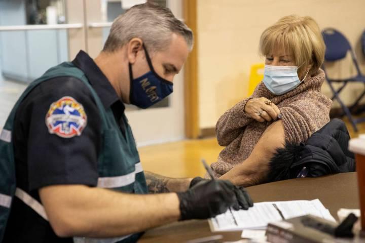 Lynne Lober, de 70 años, espera para recibir la vacuna contra COVID-19 de manos de Nathan Van ...