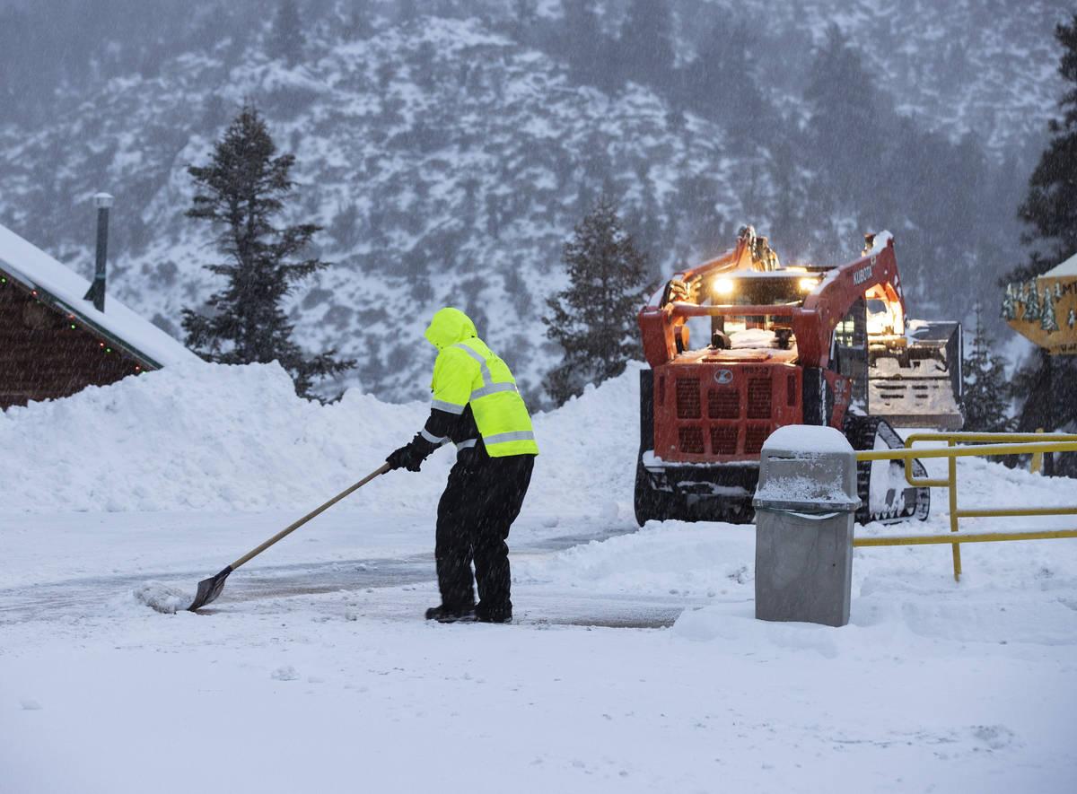 Trabajadores retiran la nieve del estacionamiento de The Charleston Lodge el lunes, 25 de enero ...
