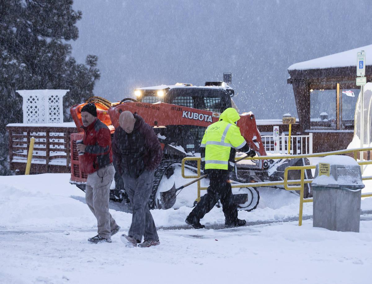 Clientes caminan por un estacionamiento cubierto de nieve al salir de The Charleston Lodge el l ...