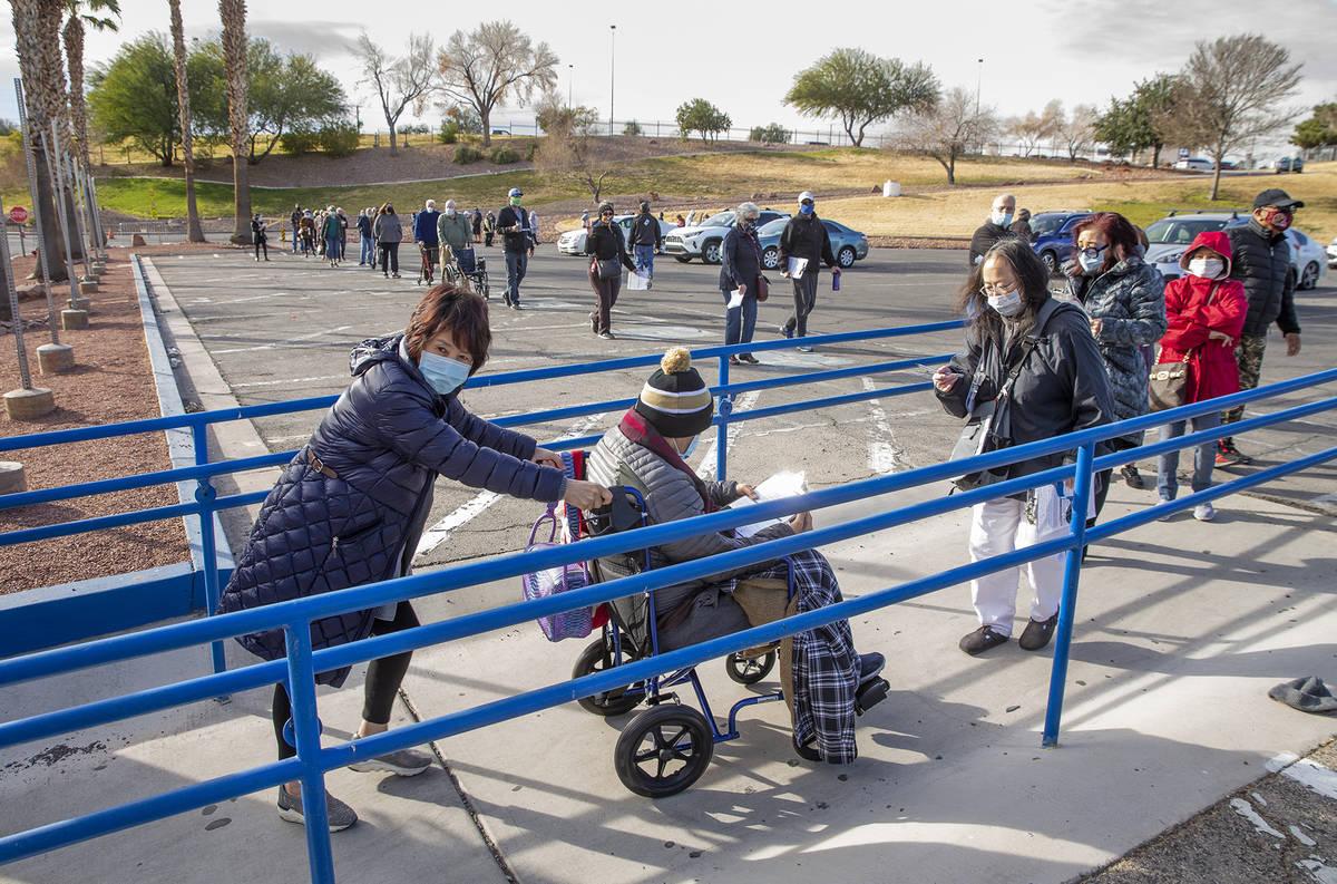 Gente avanza en una larga fila en el estacionamiento de Cashman Center para recibir las vacunas ...