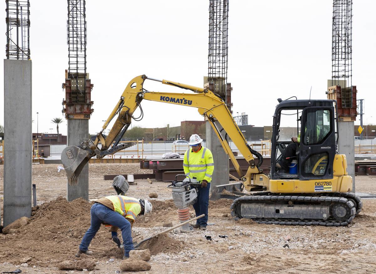 Trabajadores de la construcción utilizan compactadores para reafirmar el suelo en el sitio de ...