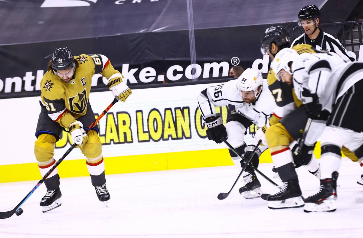El alero derecho de los Golden Knights, Mark Stone (61), patina con el puck frente al defensor ...
