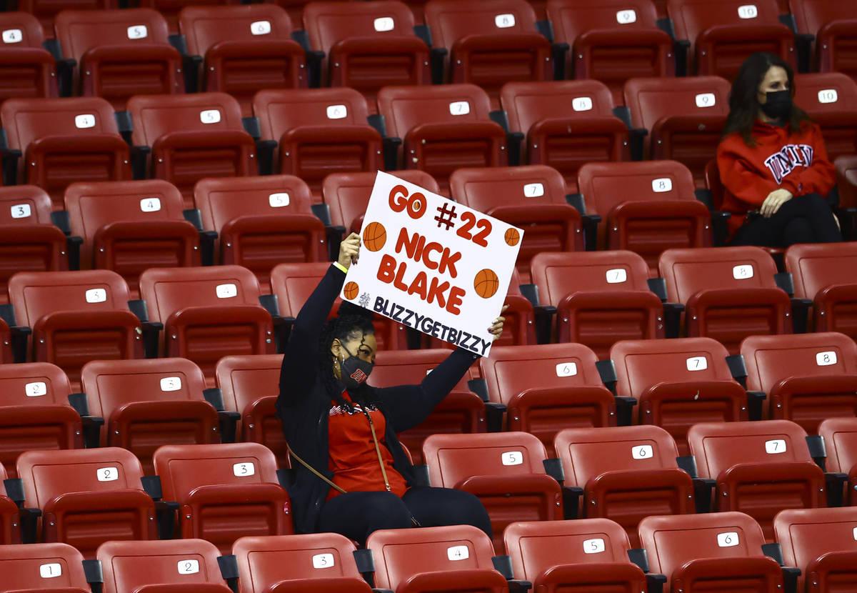 Un fan de la UNLV anima y sostiene un cartel para el escolta de los Rebels, Nick Blake (22), du ...