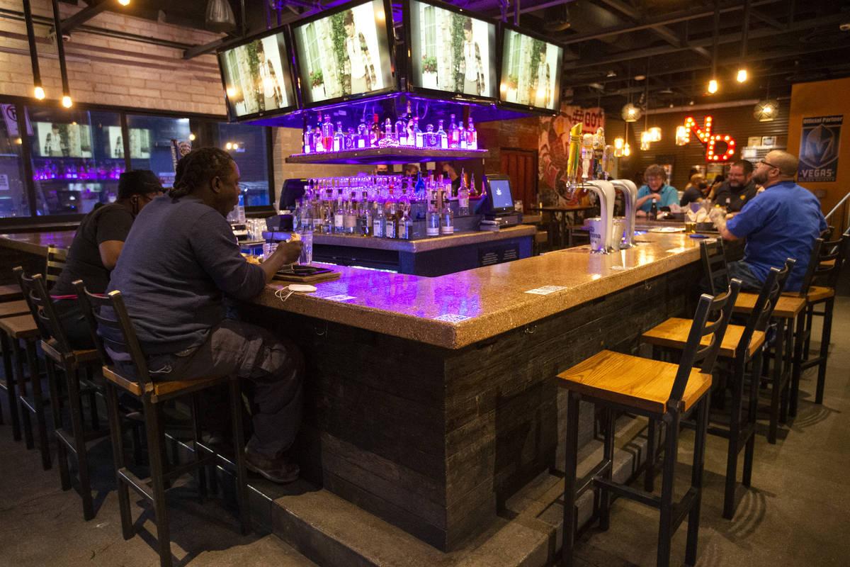 Comensales se sientan socialmente distanciados en el bar Nacho Daddy el jueves. (Ellen Schmidt/ ...