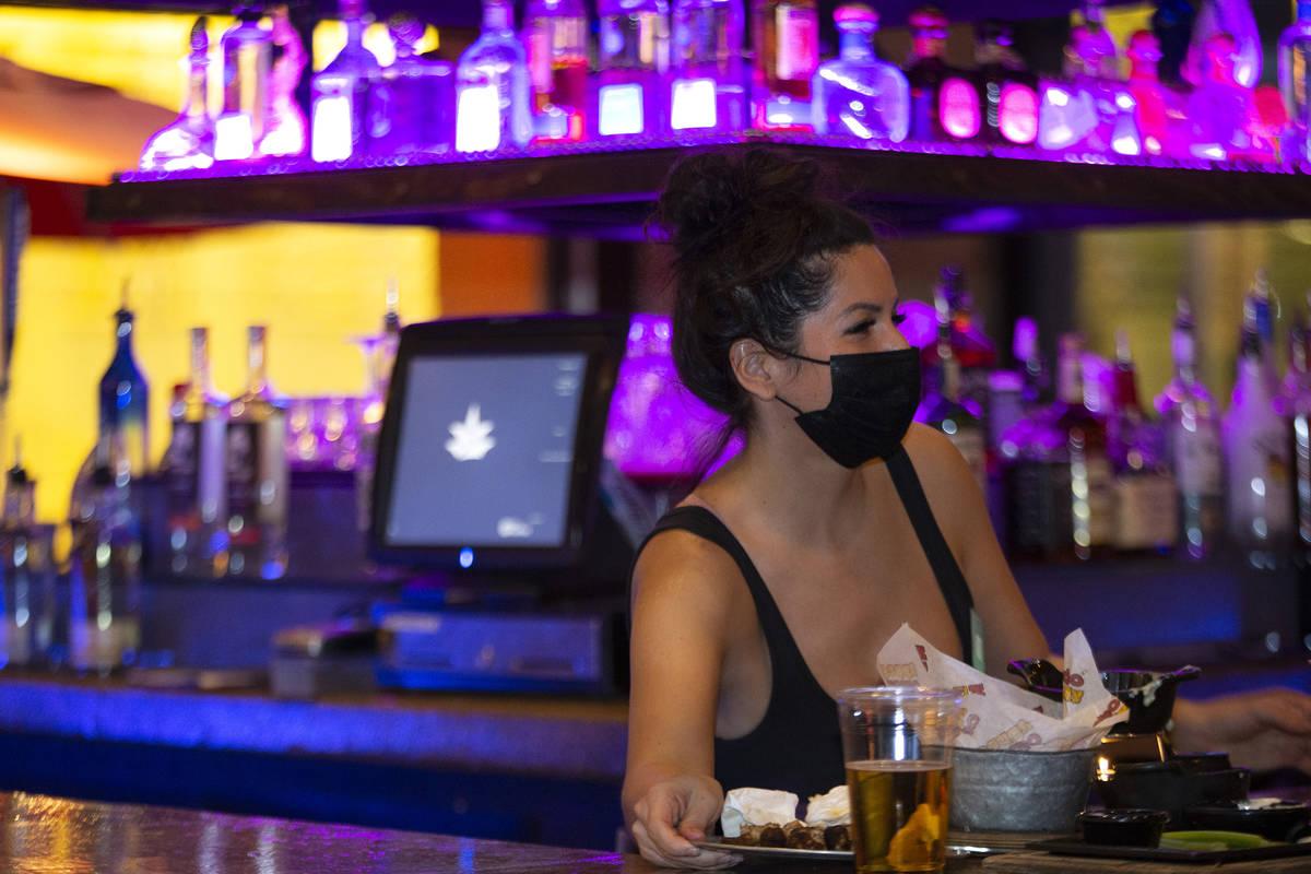 La bartender Elise Gift lleva un cubrebocas para evitar el contagio del coronavirus mientras tr ...