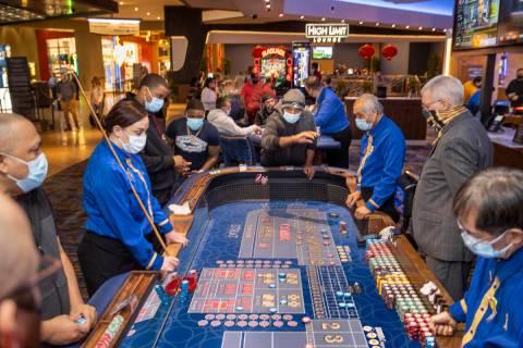 Una mesa de dados está ocupada con jugadores y croupier ya que los casinos ahora pueden acepta ...