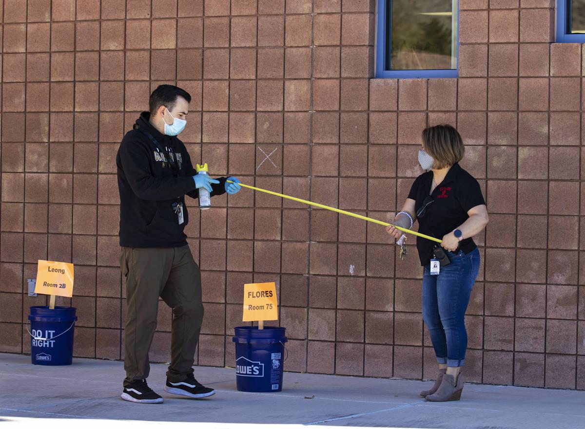 Chris Zayas, Goolsby, asistente de maestro de preescolar, rocía marcadores de distanciamiento ...