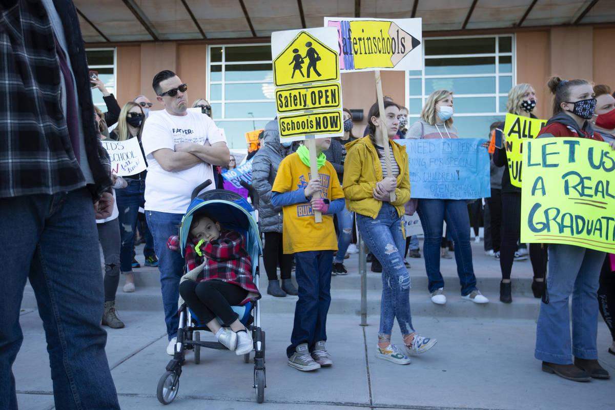 Joshua Melvin, izquierda, y sus tres hijos Emilia, Finley y Gracie asisten a una protesta fuera ...