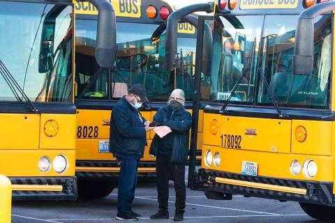 Danny Cohen, a la izquierda, y Cheryl Gorman, conductores de autobuses escolares, charlan en el ...