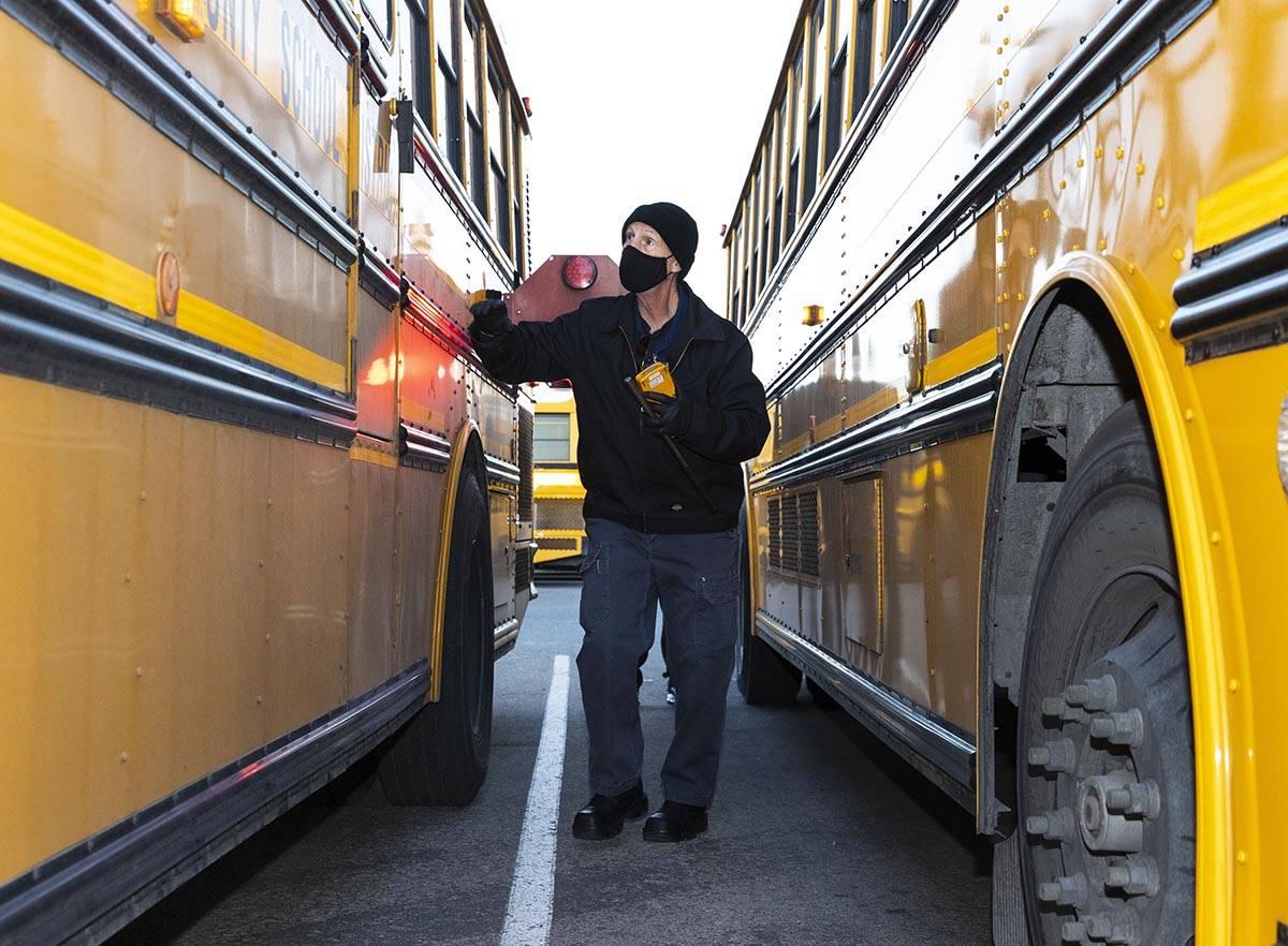 Donald Brace, un conductor de autobús escolar, inspecciona su autobús mientras se prepara par ...