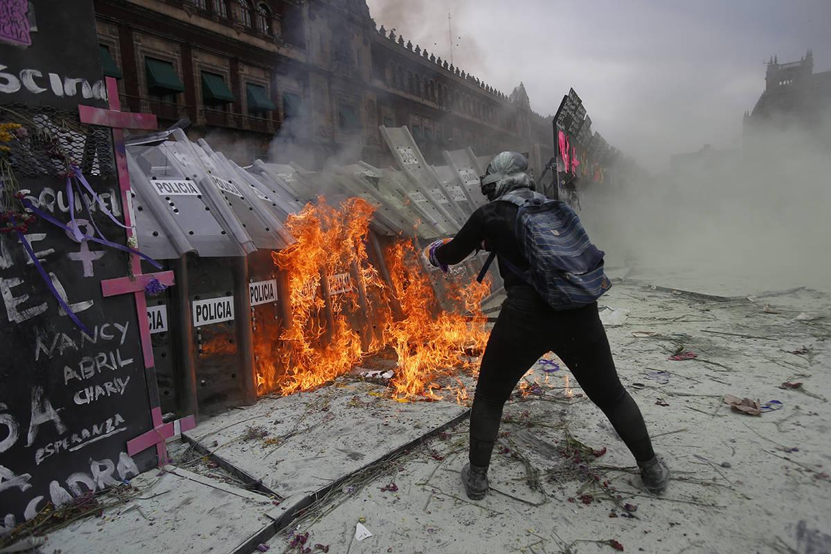 Una manifestante arroja gasolina ardiendo a un muro de escudos policiales que cierra una brecha ...