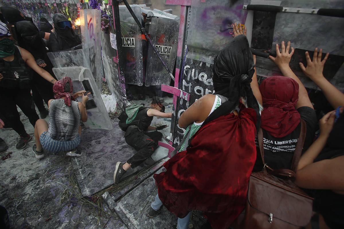 Manifestantes abren una brecha en un muro de protección policial en una barricada que protege ...