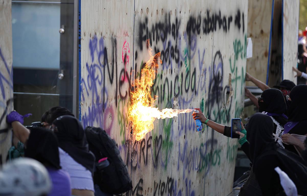 Mujeres atacan el Monumento a la Revolución de México durante una marcha para conmemorar el D ...