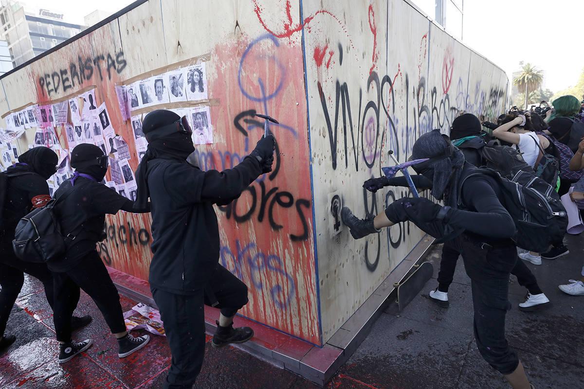 Mujeres atacan una pared de madera que protege el monumento a la Revolución de México durante ...