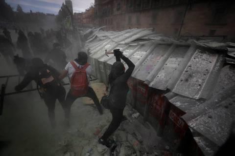 Manifestantes atacan una barricada que protege el Palacio Nacional de la Ciudad de México dura ...