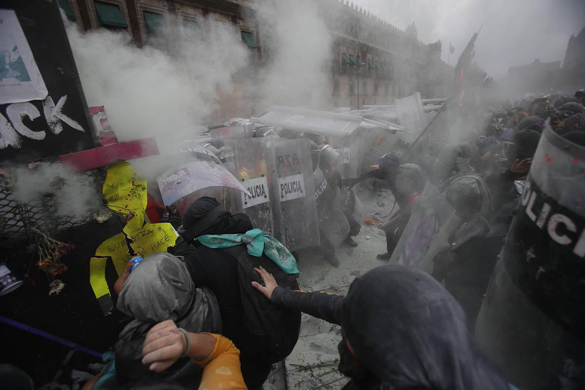 Manifestantes chocan con la policía en una brecha en una barricada que protege el Palacio Naci ...