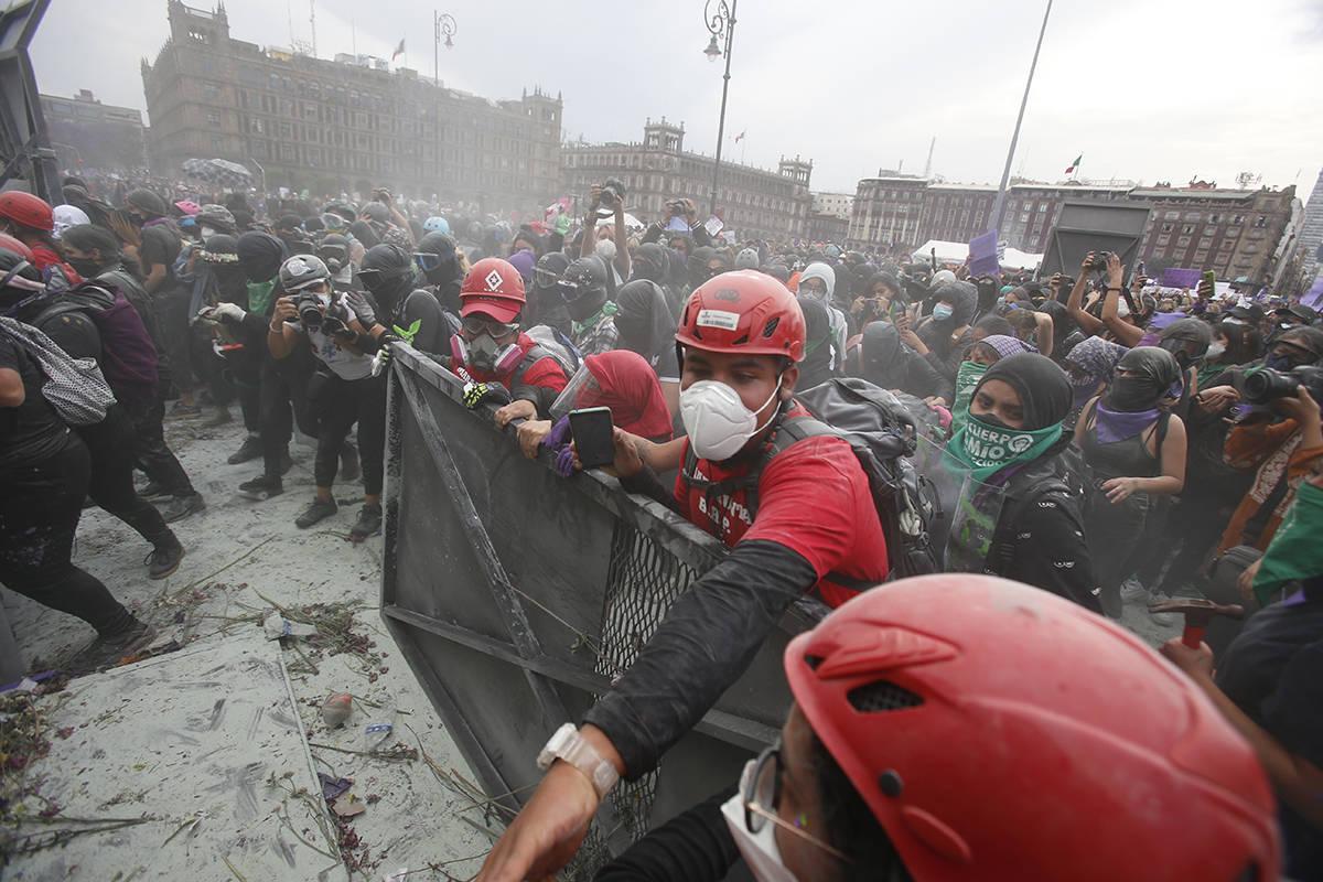 Paramédicos vestidos de rojo, intentan separar a manifestantes que chocan con la policía en u ...