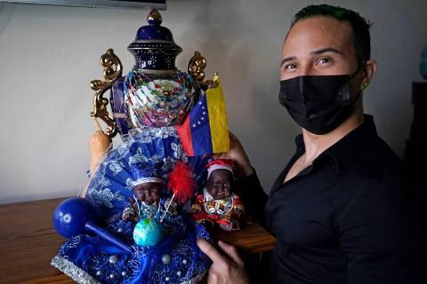 El inmigrante y peluquero venezolano Gustavo Acosta, de 36 años, posa con una bandera venezola ...