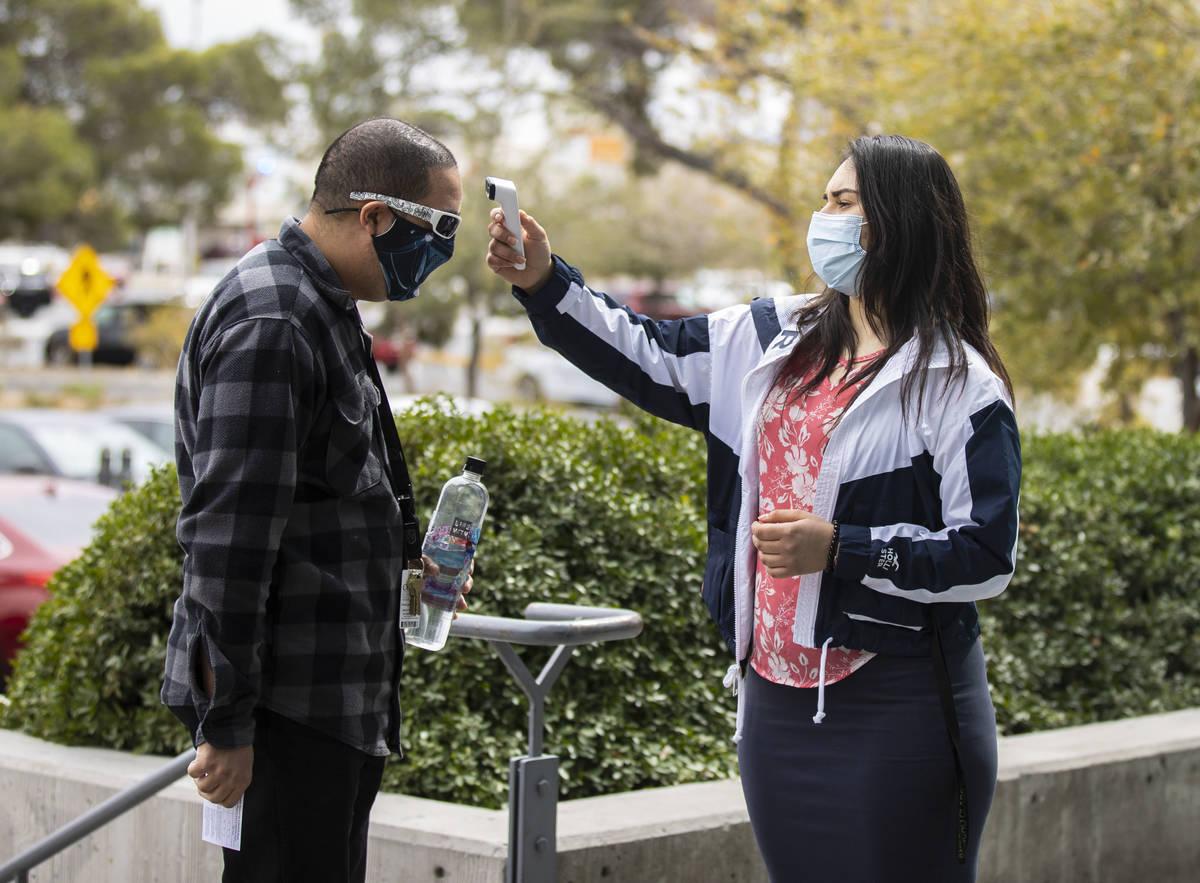 A un hombre se le toma la temperatura por Ezabai Coronado, una voluntaria, antes de tomar su va ...