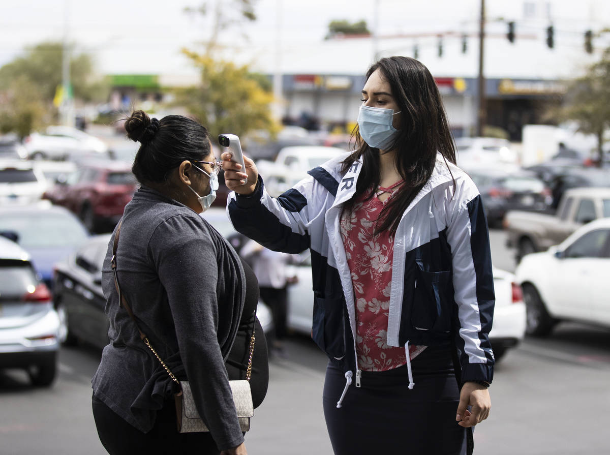 A una mujer se le toma la temperatura por Ezabai Coronado, una voluntaria, antes de tomar su va ...