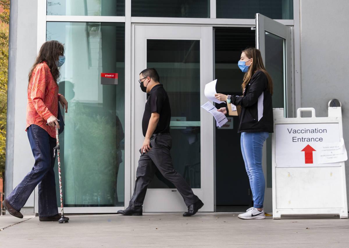 Ann Beck, a la derecha, una voluntaria, se prepara para entregar los formularios de consentimie ...