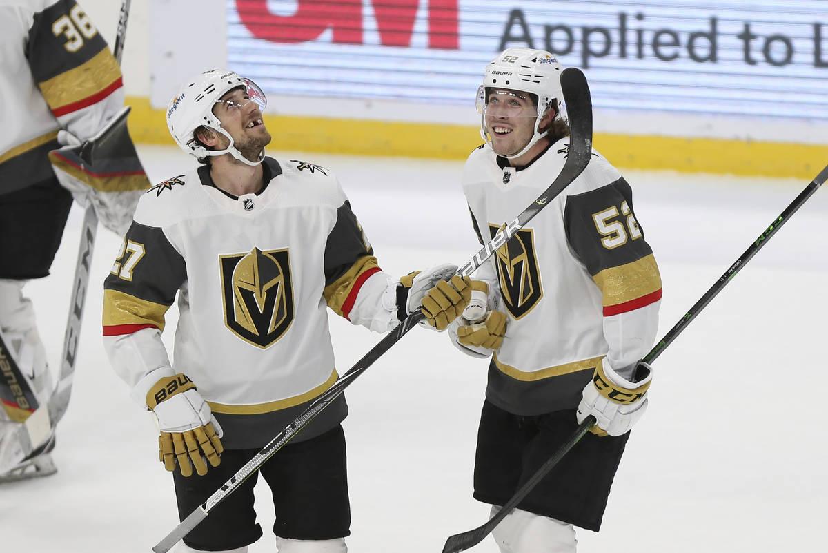 Dylan Coghlan (52), de los Vegas Golden Knights, sonríe con su compañero Shea Theodore (27) d ...