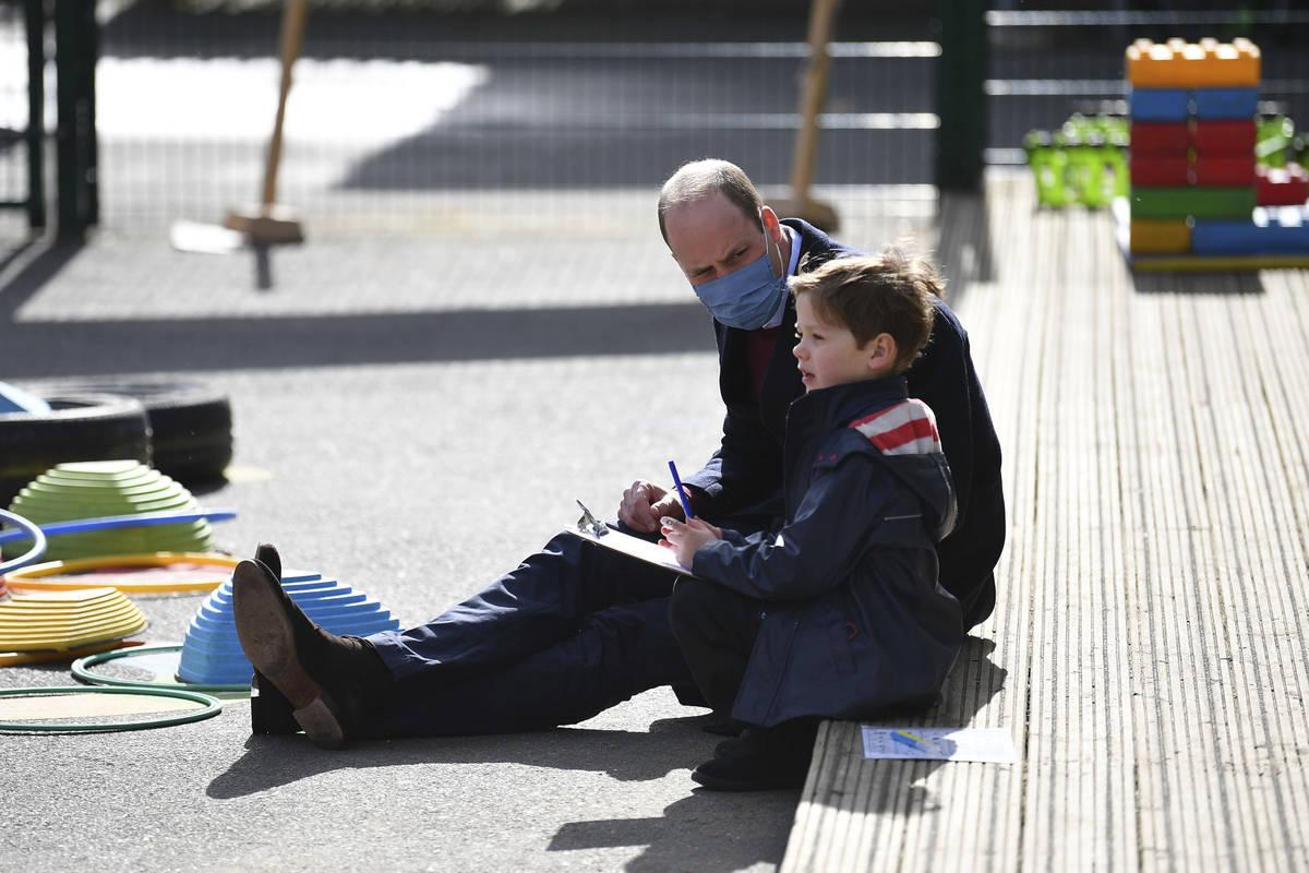 El príncipe británico William habla con un niño en el patio de recreo durante una visita con ...