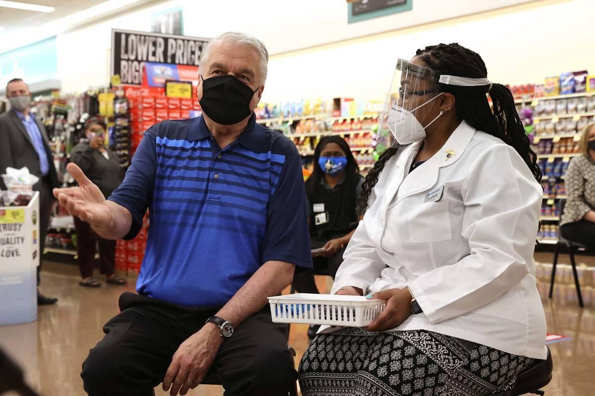 El gobernador Steve Sisolak visita a la gerente de farmacia, Trashelle Miro, antes de recibir s ...