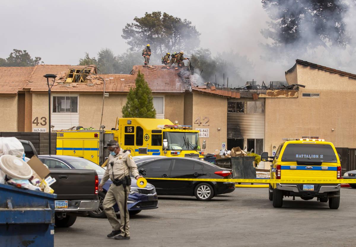 Los bomberos del Condado Clark y del Las Vegas Fire Department trabajan en la escena del Buildi ...