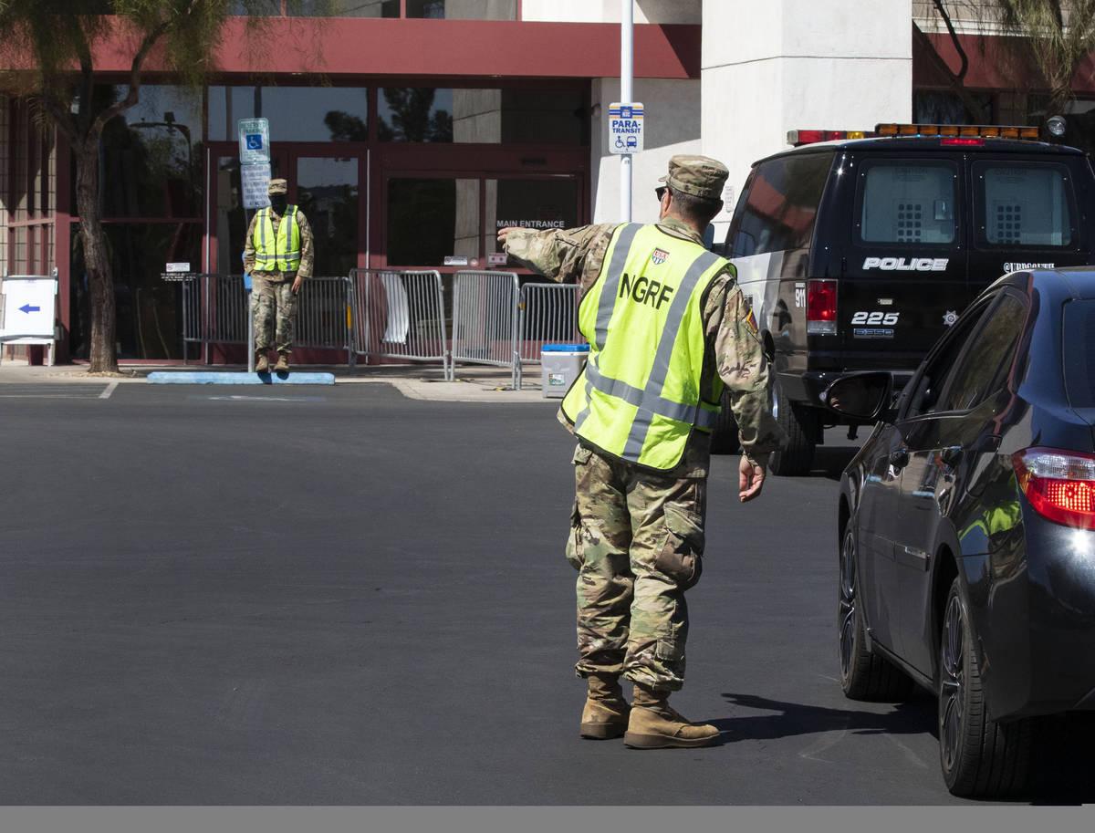 Un miembro de la National Disaster Response Force dirige el tránsito mientras una camioneta ll ...