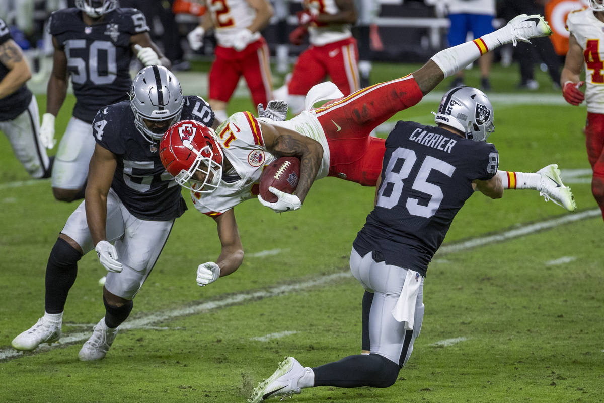 El wide receiver de los Kansas City Chiefs, Demarcus Robinson (11, centro), es derribado por el ...