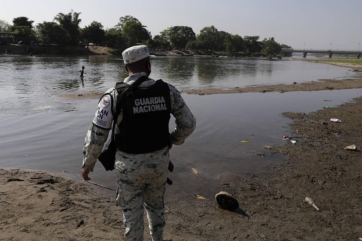 Un miembro de la Guardia Nacional Mexicana se encuentra en la orilla del río Suchiate, la fron ...