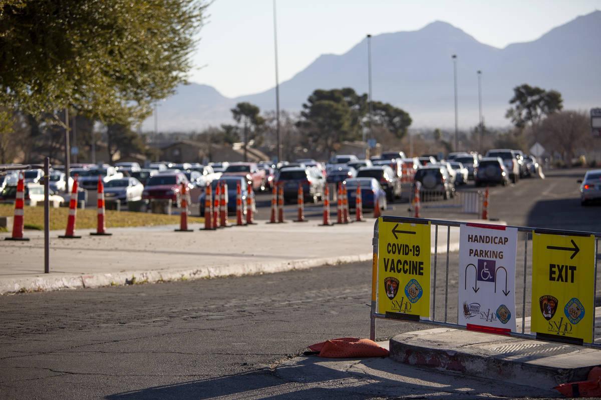 Unos carteles indican dónde ir para conseguir la vacuna contra COVID-19 con un estacionamiento ...