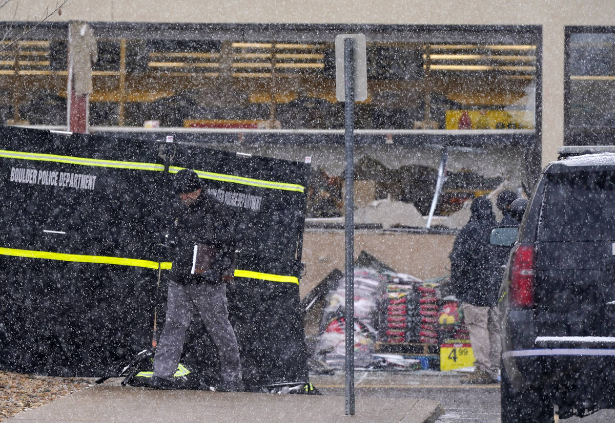 Investigadores se enfrentan a una ligera nevada mientras recogen pruebas en el estacionamiento ...