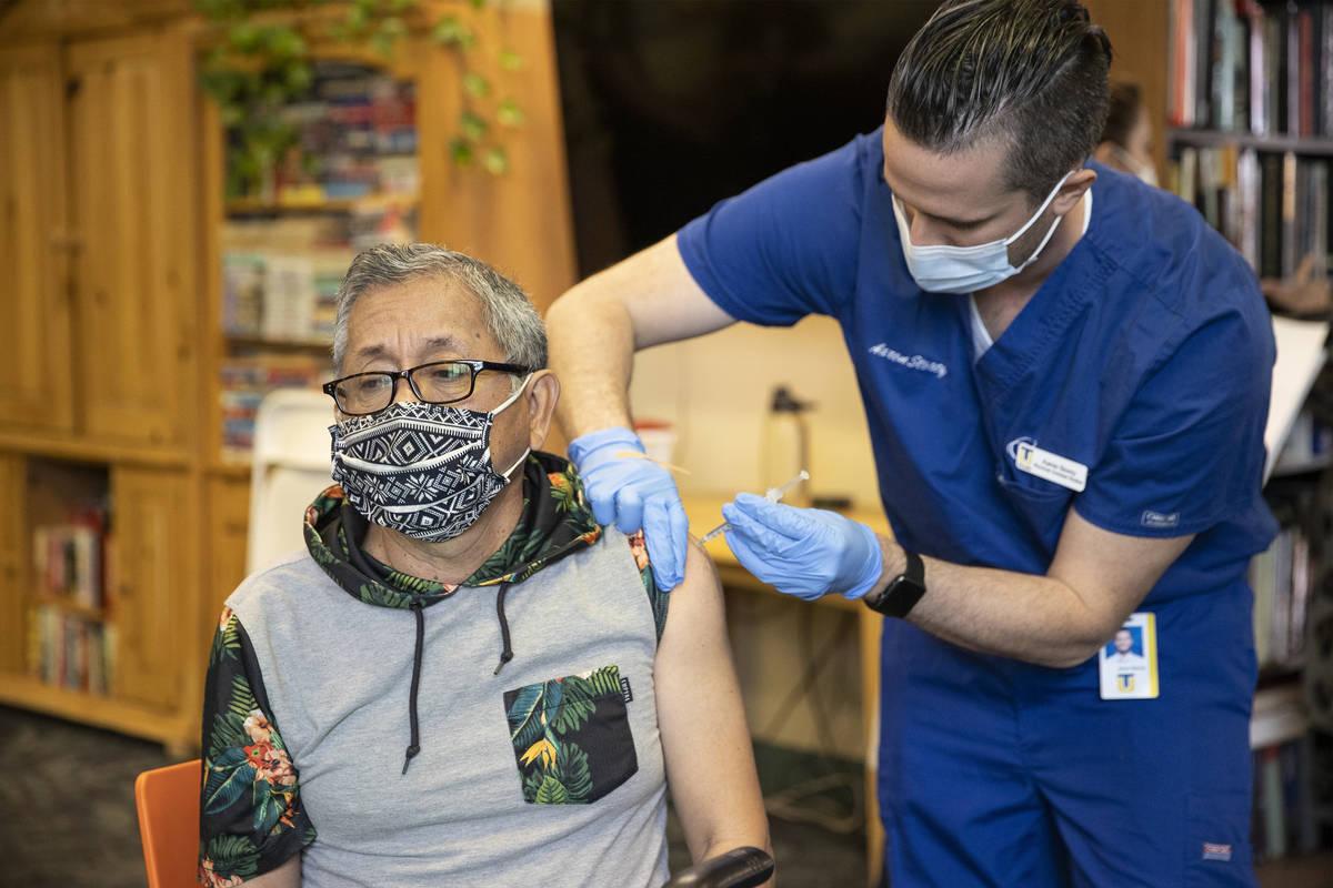 Leonardo Terravova, de 66 años, recibe la vacuna contra COVID-19 de Aaron Storey, estudiante d ...