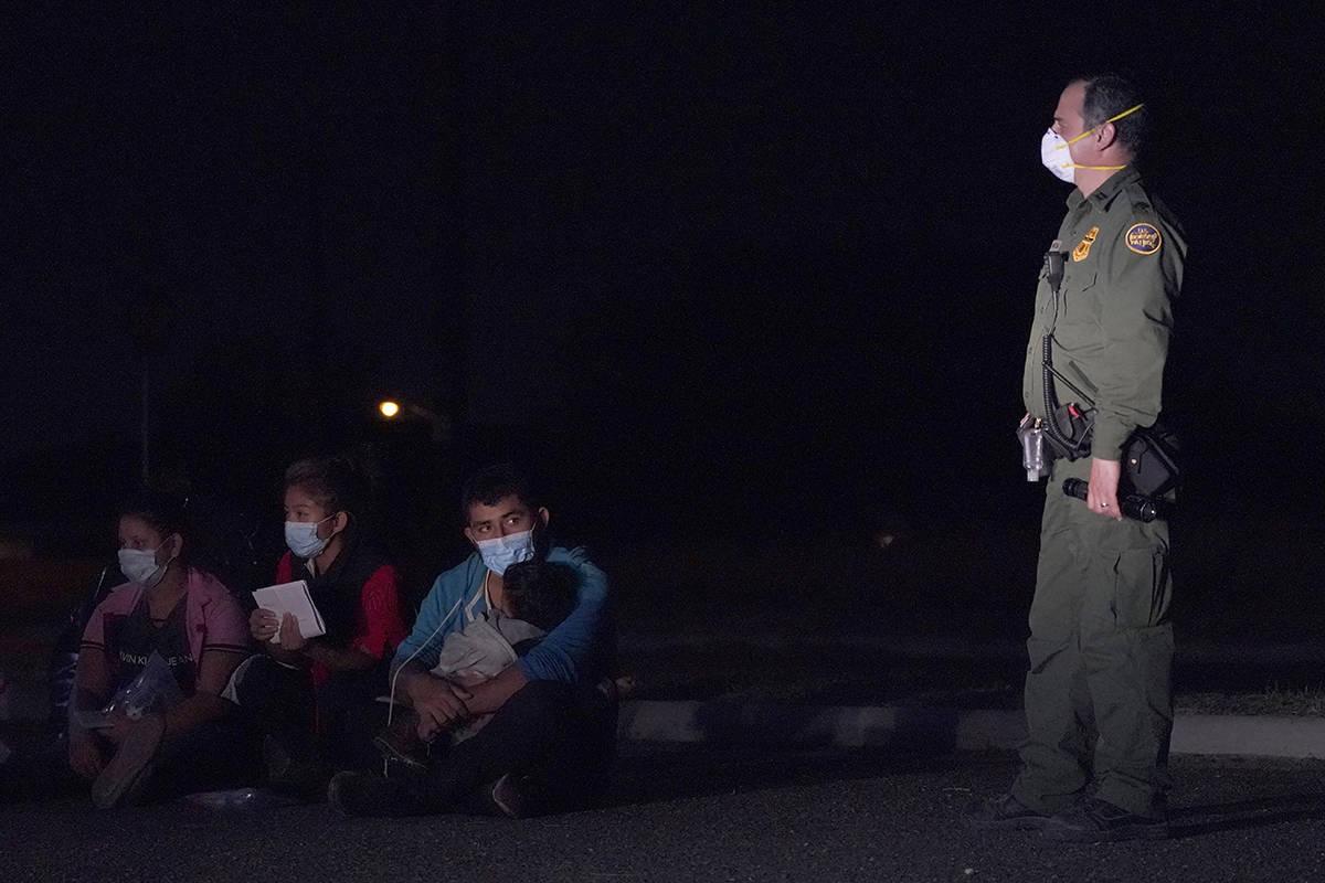 Un hombre migrante, en el centro, sostiene a un niño mientras mira a un agente de Aduanas y Pr ...