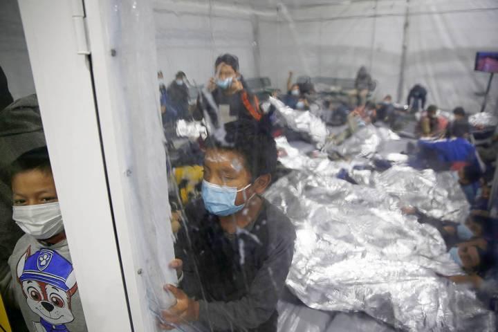Niños pequeños observan desde el interior de una cápsula en el centro de detención del Depa ...