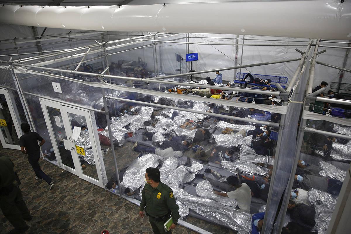 Los niños pequeños se paran o duermen dentro de una cápsula en el centro de detención de Ad ...