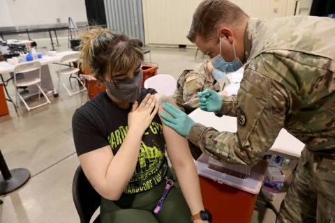 Micah Haji-Sheikh, de 27 años, de North Las Vegas, recibe la vacuna contra COVID-19 por parte ...